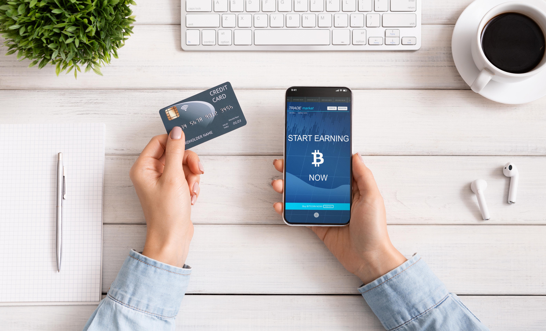 woman-using-credit-card-and-bitcoin-earning-mobile-LWV3PBU